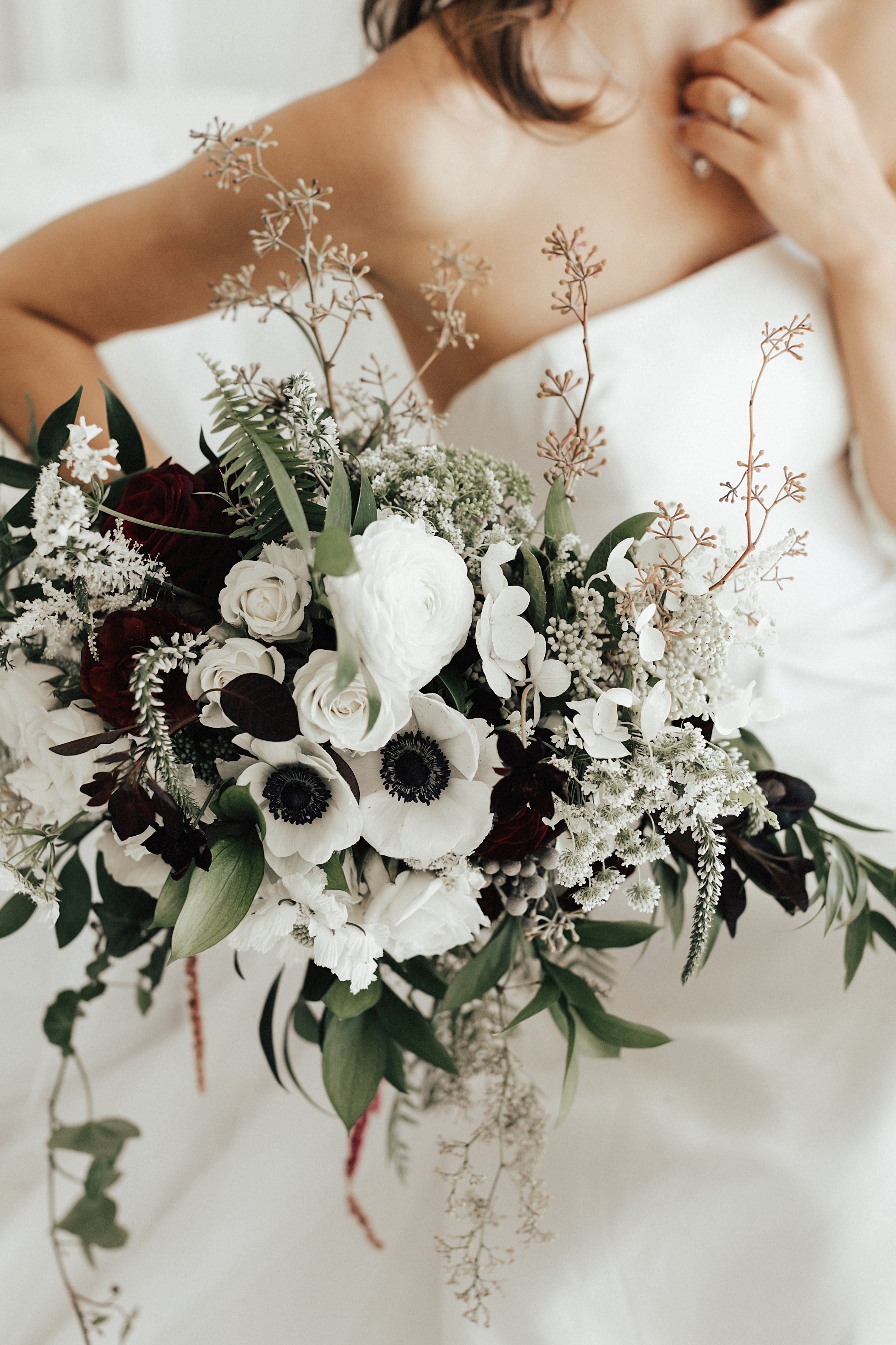 White Anemone Bouquet With Accents Of Dark Greenery And Burgundy