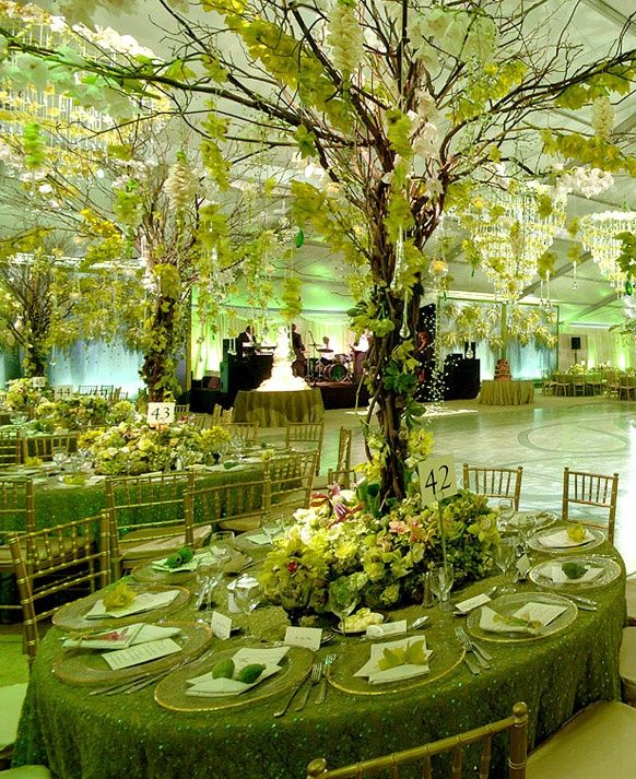 A green wedding reception. Lots of natural touches to the tablescape elevating the eye upward from the tree-inspired centerpieces. & Great use of a tree in the middle of each table with floral sprays ...