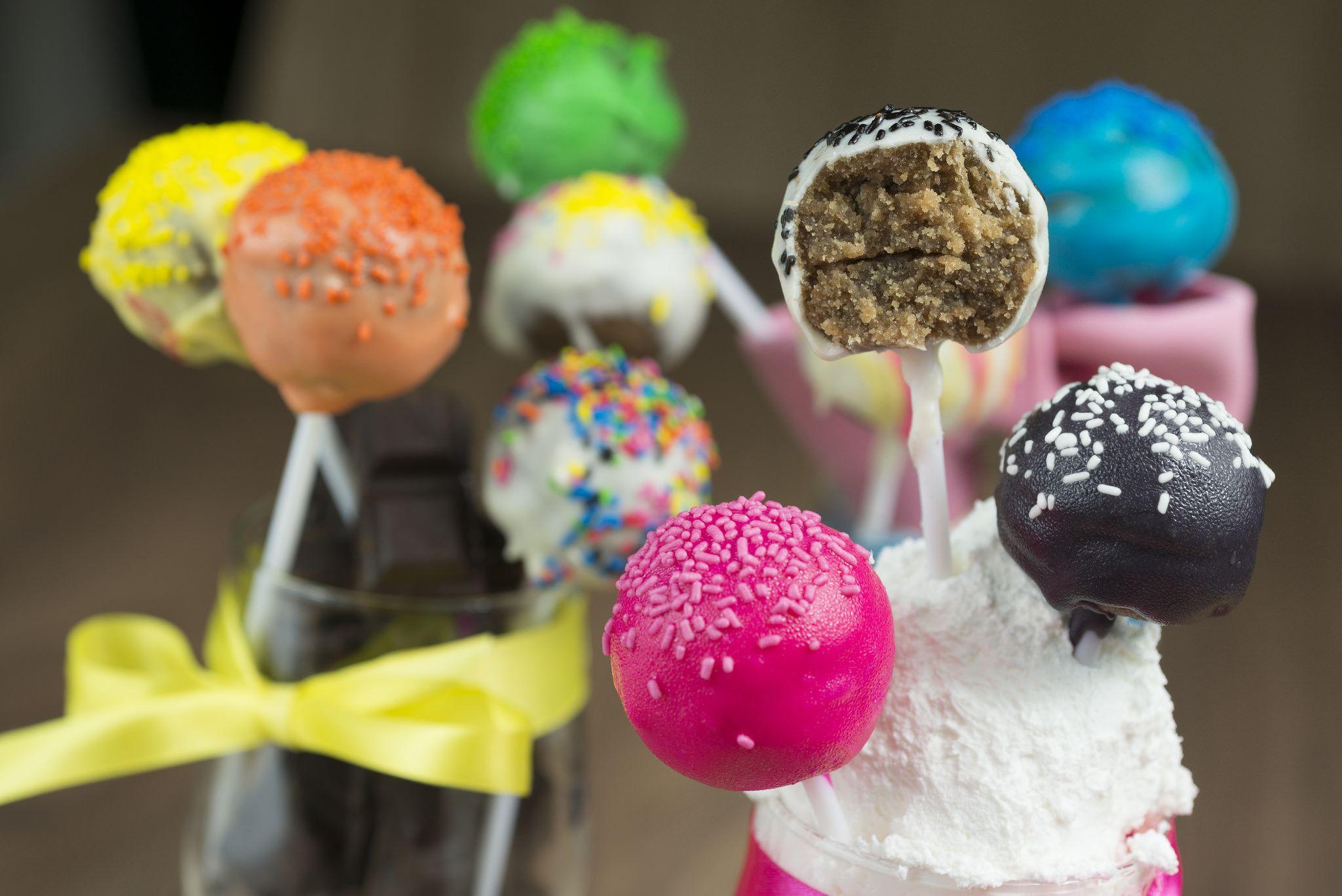 Cake pops možete poručiti i kod nas, u sastavu imaju rastresiti, drobljeni patišpanj uz dodatak euro krema, čokolade i ukusa pomorandže. Glazura je čokoladna i u bojama koje vi odaberete.