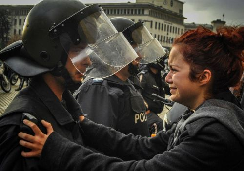 Photo turned into a cult. Student, part of a peaceful protest, holding one of the officers protect students from violence of his colleagues.