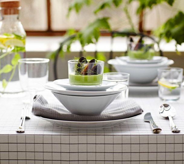 Bord dukat med tallrikar i vitt fältspatporslin, glas samt bestick i rostfritt stål.