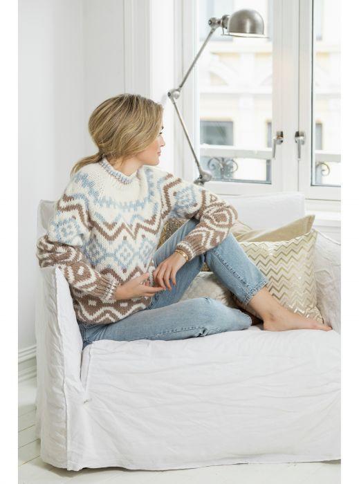 Camilla Pihl som sitter i en sofa og ser ut av vinduet. Hun har på seg Bluebell genser Summer Breeze, i Camilla Pihl Olava, fra House of Yarn. #strikkeoppskriftgenser