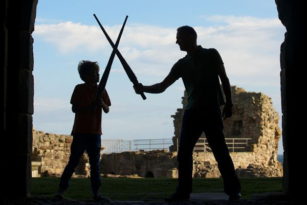 A man and a child dueling with swords
