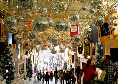 shoppers walk through christmas decorations at a shopping mall ap