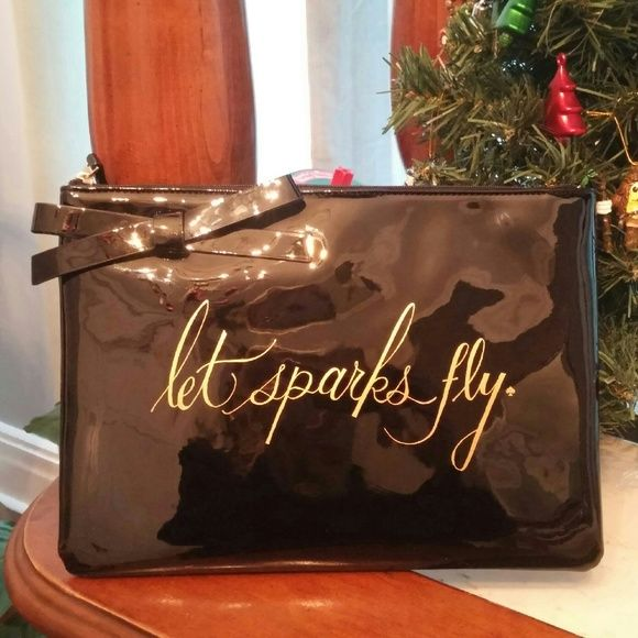 """Kate Spade Let Sparks Fly Georgie Clutch New with tags, authentic Kate Spade """"Let Sparks Fly"""" Bow Georgie in shiny black pvc.  This patent pouch is printed with 'Let sparks fly' in gold foil.  ~ Front bow applique. ~ Back signature staple in 12k plated gold.  ~ Flat clutch with a zip top closure. ~ Lined. ~ Measures 8''h x 11''w x 0.6''d kate spade Bags Clutches & Wristlets"""