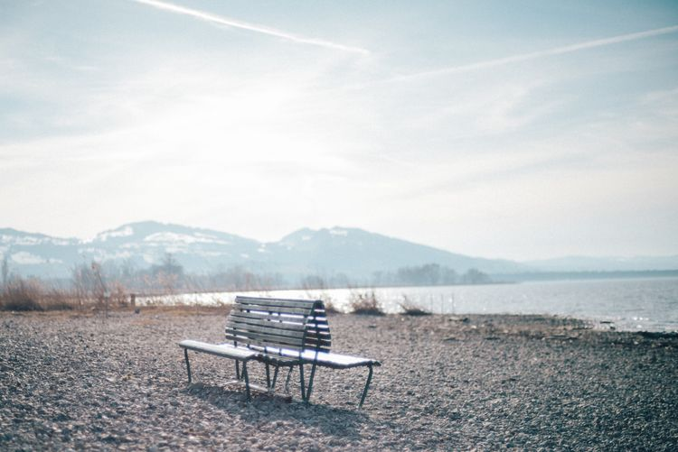 Bench facing the landscape of the mountains surrounding the Bodensee in the border between Switzerland and Austria