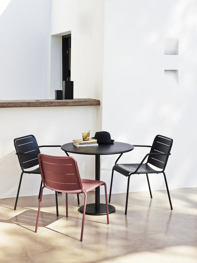 Table ronde en métal noir chaises design assorties et modèle métallique rouge