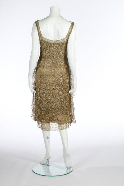 Chanel gold lace cocktail dress, circa 1924, the gold lamé slip with yellow on ivory satin woven 'Gabrielle Chanel' label, numbered 6571, the underslip with lace trimmed hem and lead weights, the gold guipure over-dress edged in gold braid and with gold lace flounce running across the rear dropped waist and down the sides. The lead weights at the hem are covered in gold fabric. Braid is used to edge hem and as inserts down side seam.  Back 4