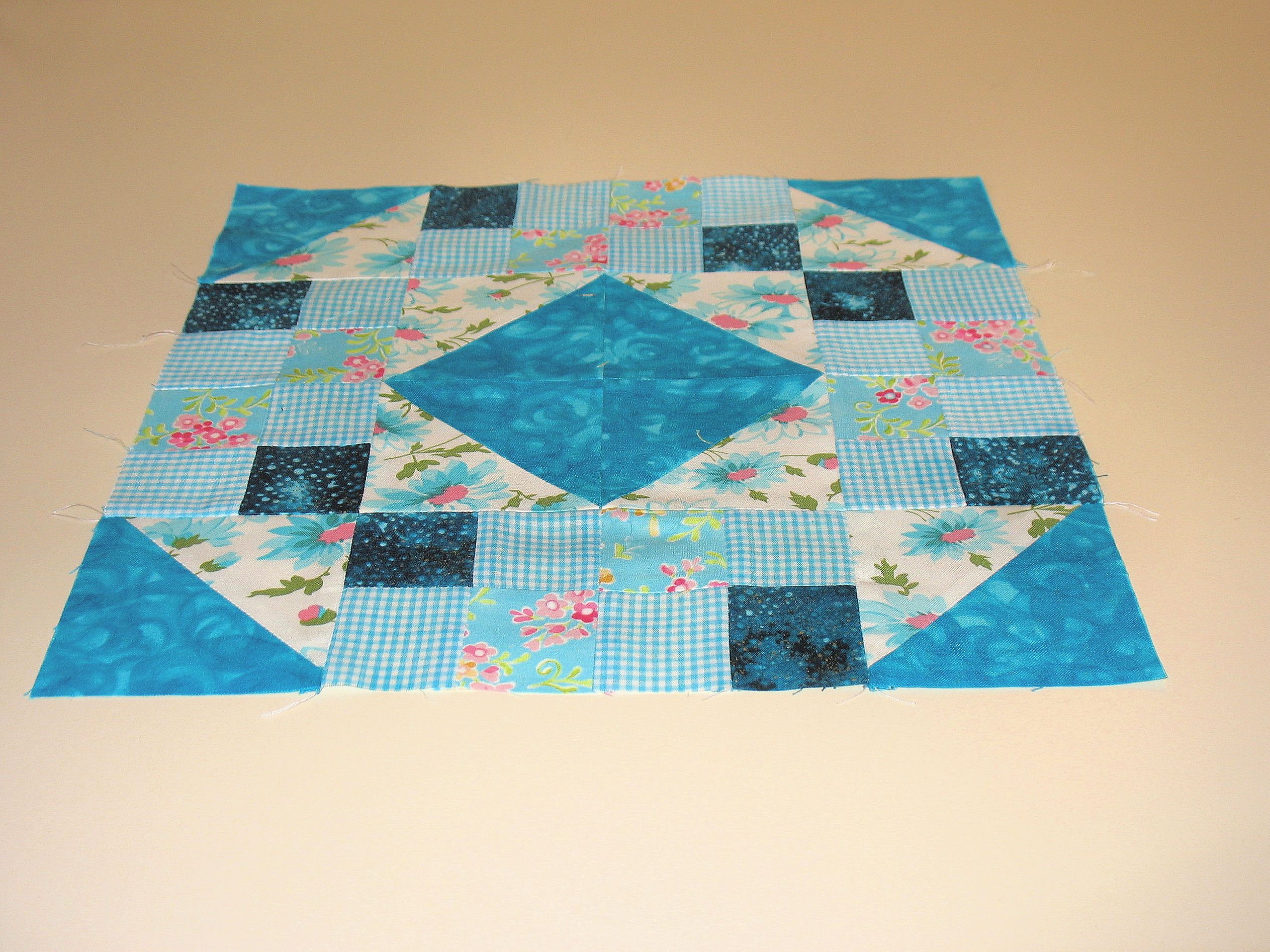 "A traditional block pattern called ""Jewel Box"" pieced by Pam Wilson in September  2014, incorporating gingham and other fabrics from the stash of my aunt Johanna Wackerle Tanner."