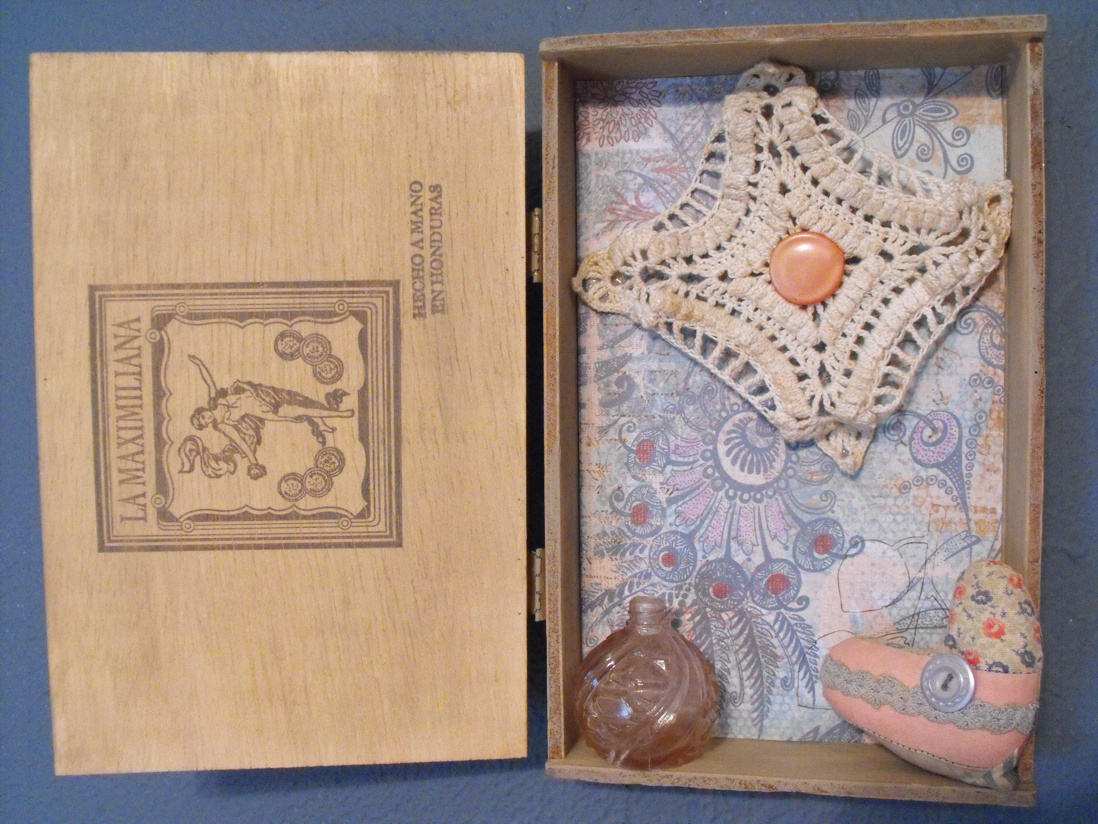 An old cigar box that I lined with scrapbooking paper, added a doily & button, plus other items I had collected.