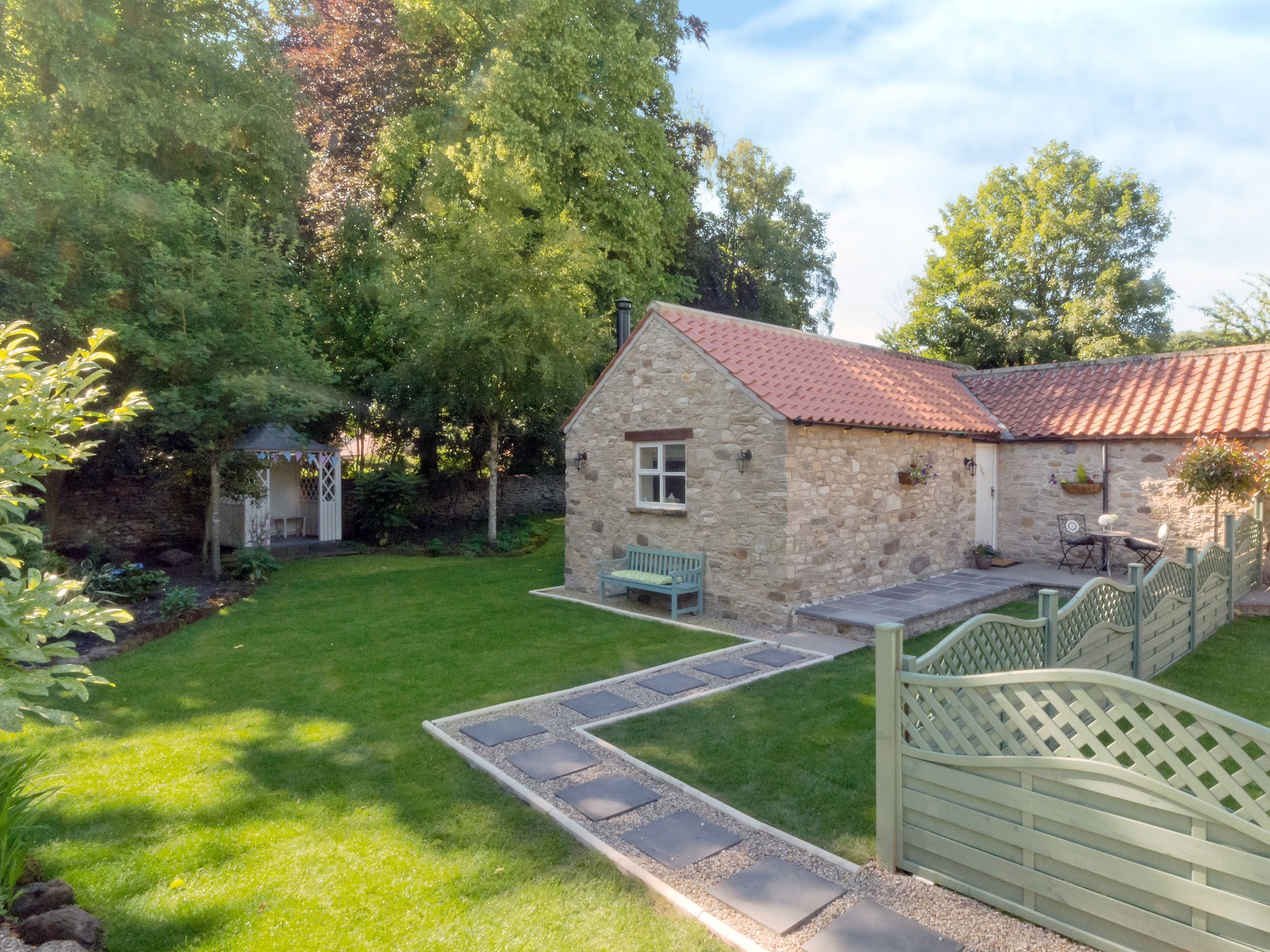 Snuggle up in front of the wood burner whilst admiring the gardens of this quaint holiday cottage.