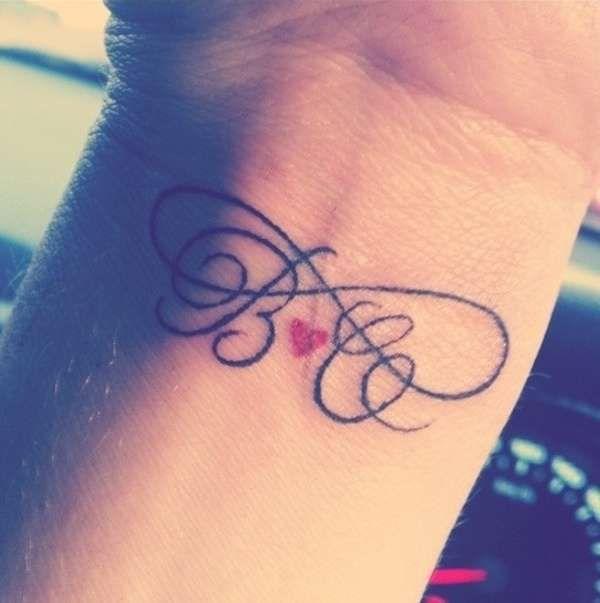 Tatuaggio con iniziali di nomi intrecciate , Tatuaggio con iniziali  incrociate e cuoricino. Simbolo Infinity