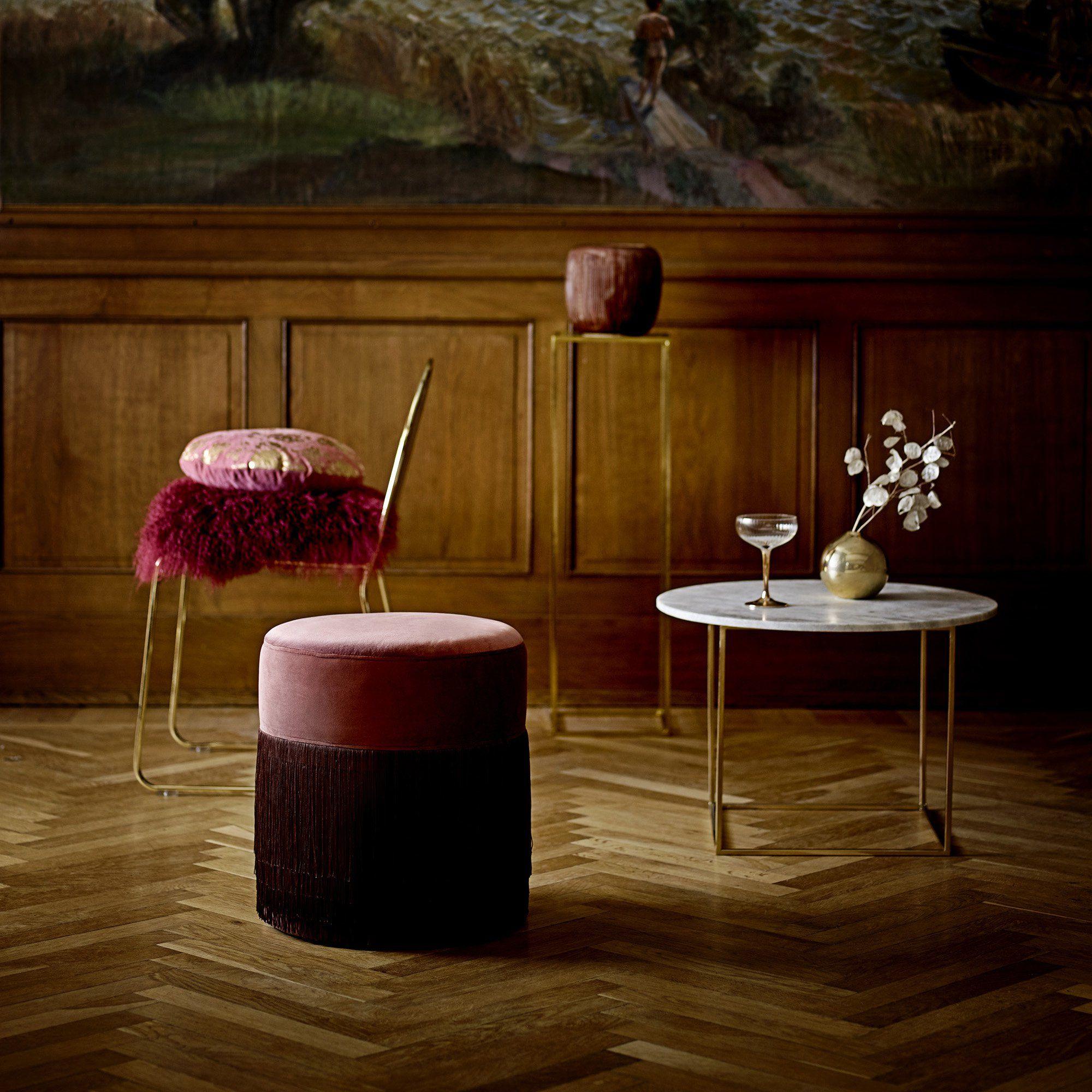 Un pouf à frange rond et de couleur bordeaux dans un salon parisien ...