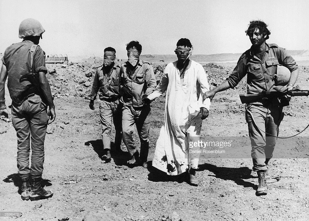 1973: Three barefoot, blindfolded Egyptian POWs are led to the western side of the Suez Canal by an Israeli soldier as another soldier looks on during the Yom Kippur War, Middle East. One of the POWs wears a long, blood-stained dishdash or Kaftan. Israel