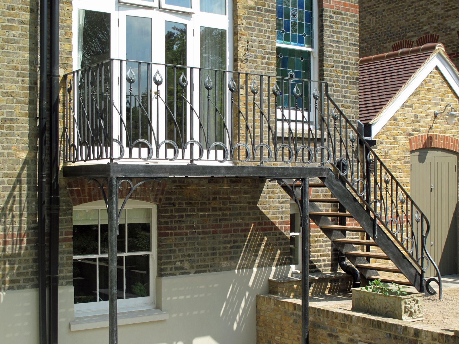 Bespoke architectural ironwork balcony and stairs for a Wimbledon town  house. The design of this forged metalwork balcony echoes the garden beyond.