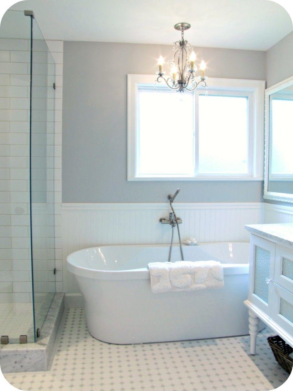 Bathroom. white acrylic freestanding bathtub under small chandelier ...