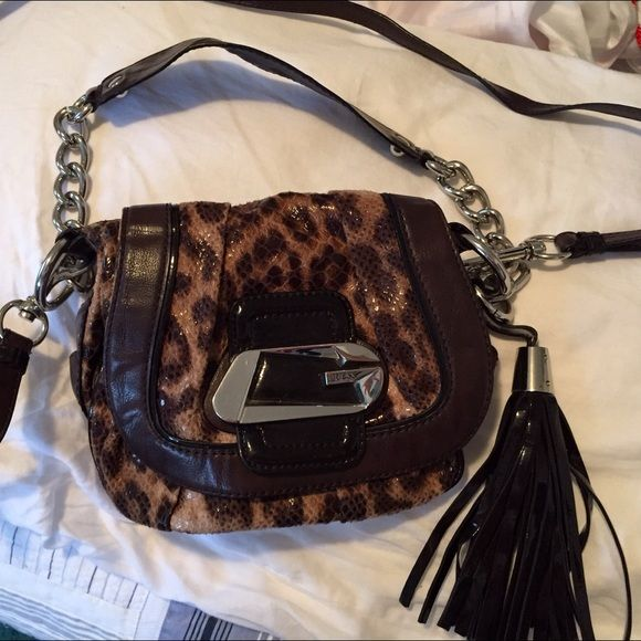 Guess Animal print - excellent condition This bag has 1 zippered pocket and 1 cell phone pocket. The material is a soft suede with a clear snake skin print over it. It is a cute bag and a good size. It has a 6 inch drop handle and a removable shoulder strap that is also adjustable. Magnetic clasp, Metal is silver toned. Make me a reasonable offer Guess Bags Crossbody Bags