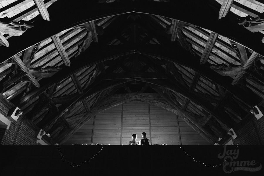 Couple backlit and with fairylights on the Weaver Gallery, inside New Guesten Hall at Avoncroft Museum of Historic Buildings (avoncroft.org.uk). Black and white photograph. Jay Emme Photography.