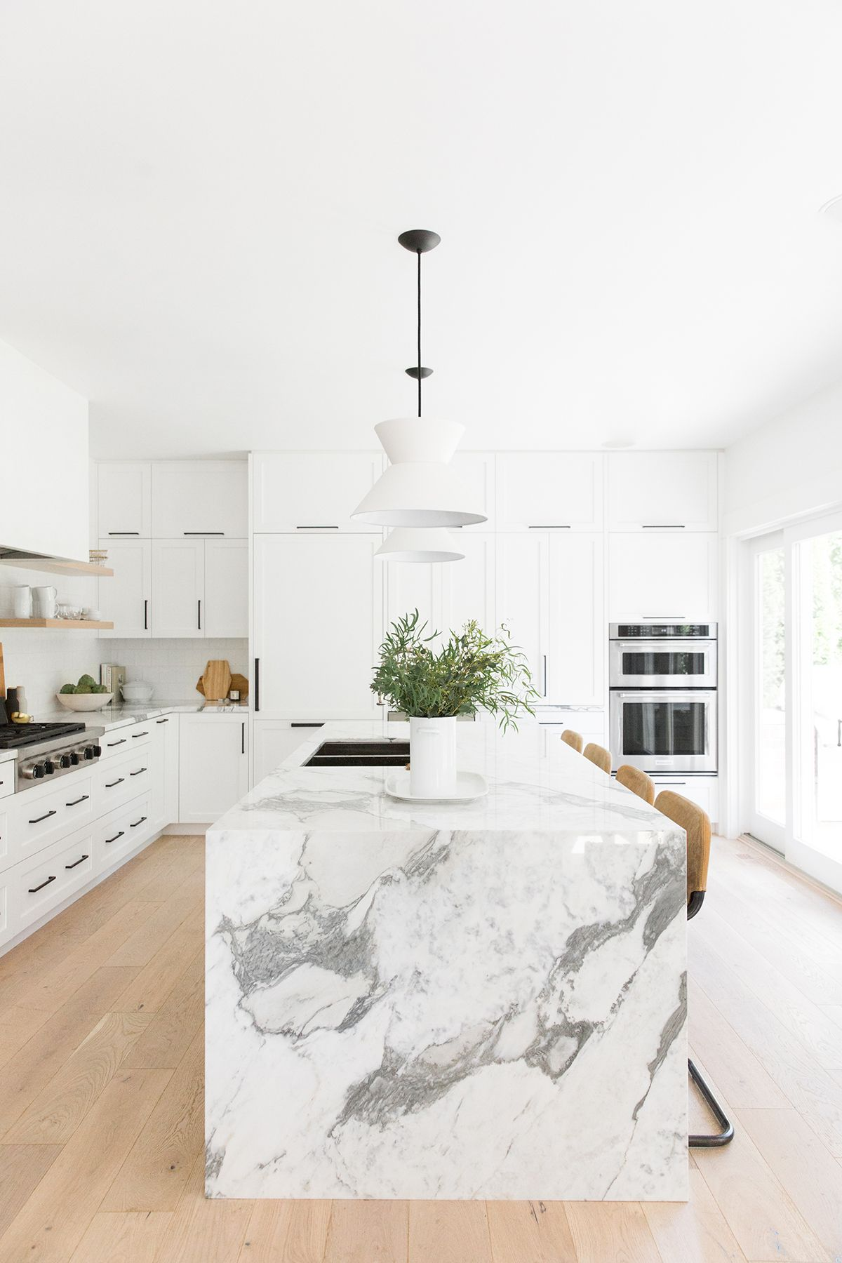 Light, natural, modern white kitchen with leather stools and a thick marble island, natural wood open shelving, concrete hood | Studio McGee Design Blog