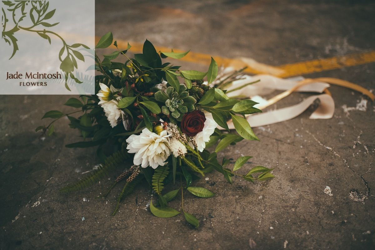 textured organic bouquet in ivory, red, blue and burgundies with trailing ribbons in ivory, cream and golds