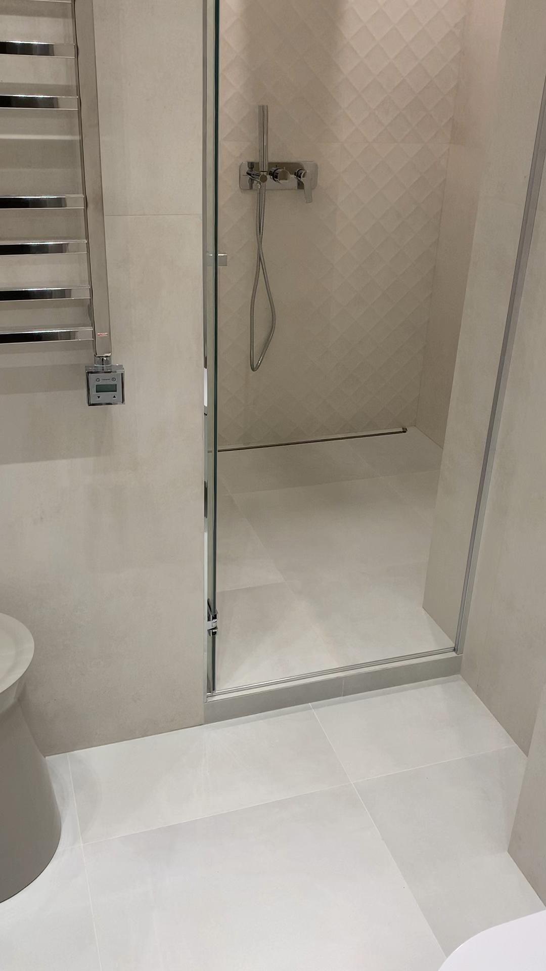 Ремонт ванной комнаты. Душевая зона с дверью из стекла.