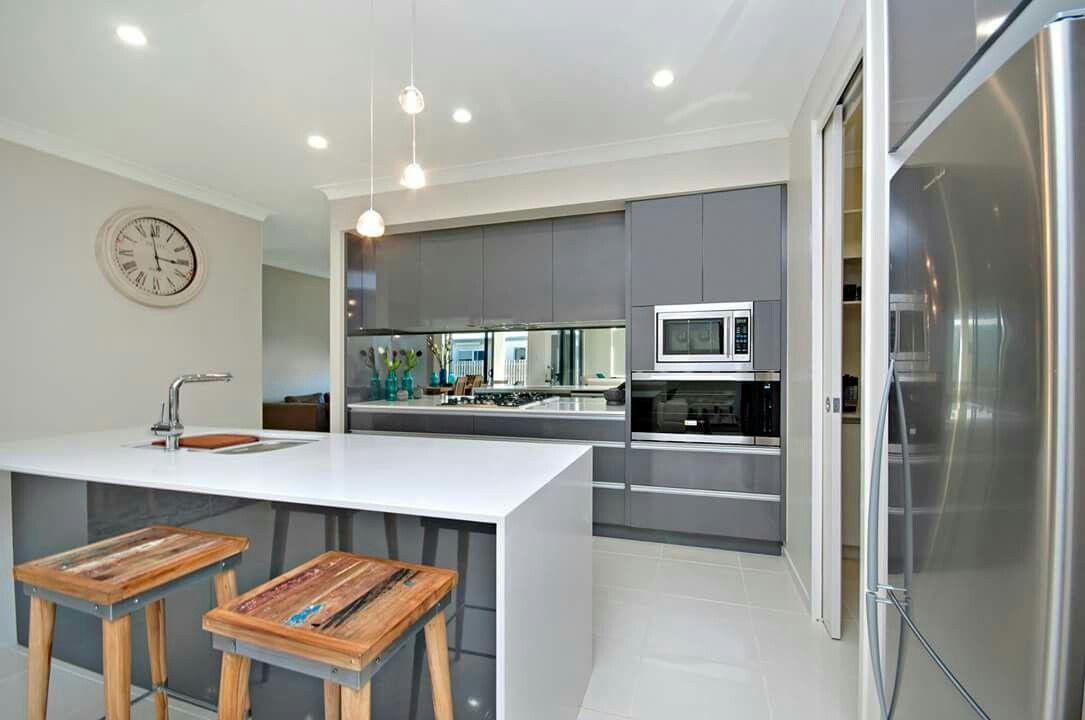 White Kitchen Mirror Splashback gloss grey kitchen with white stone benchtops and smokey mirror