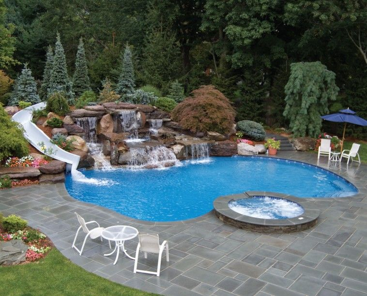 residential pool with waterfalls and white curved water slide on rock combined with spa pool with