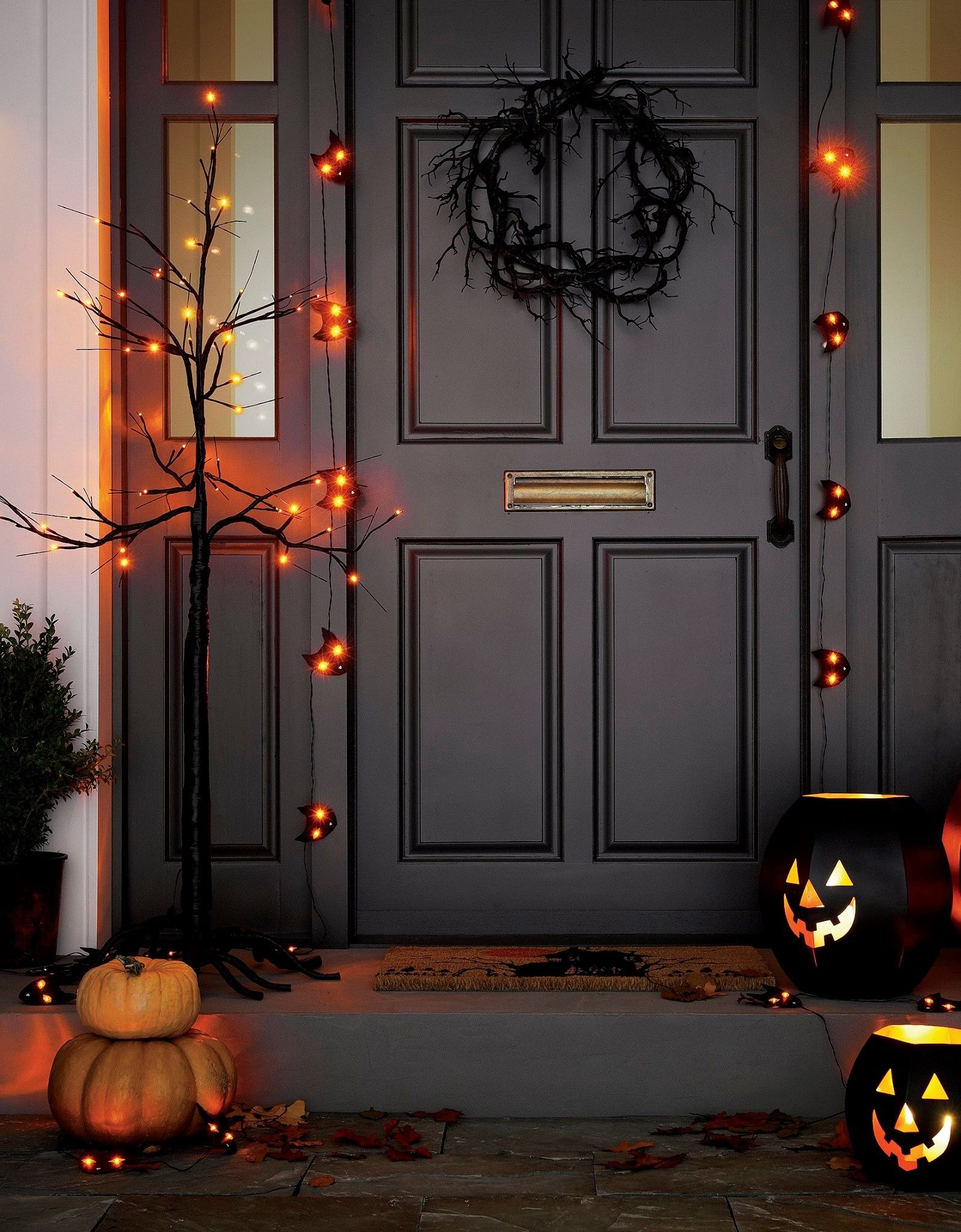 orange led lights add spooky illumination to bare branched black halloween tree decoration that can be set up indoors or out