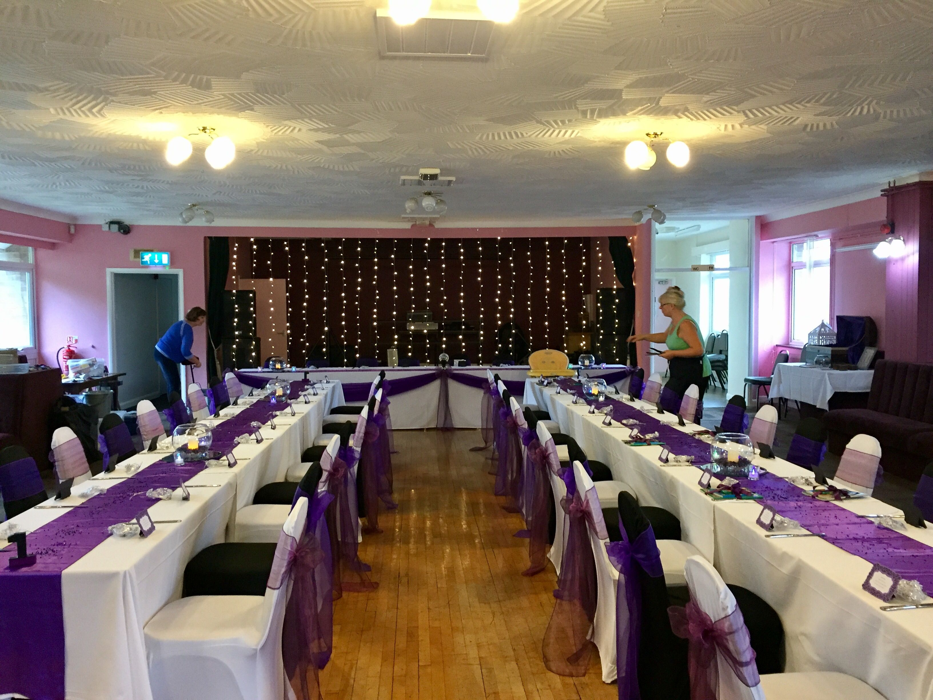 Black and white cover with purple sashes, fishbowl centrepieces and fairy lights.