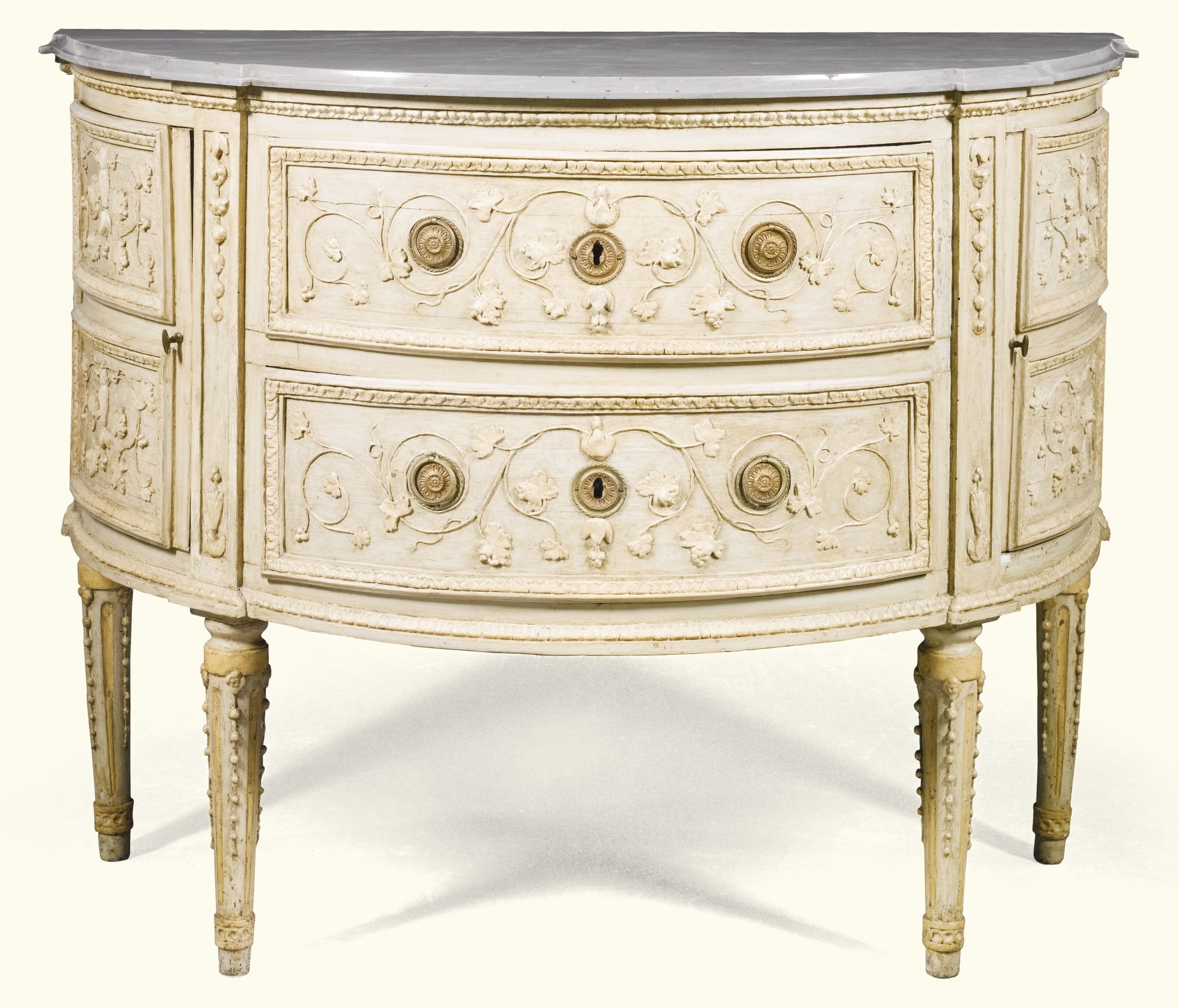 An Italian cream and ivory painted demi-lune commode, Piedmontese, late 18th century with a moulded bleu turquin marble top above two drawers carved with scrolling foliage flanked by cupboard doors, the stiles with trails of husks on fluted and beaded tapering legs terminating in toupie feet;.