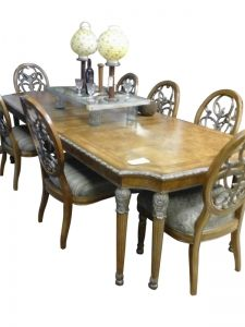A classic style dining set, complete with nine chairs, a table and two leaves. The table top features parquet decoration,
