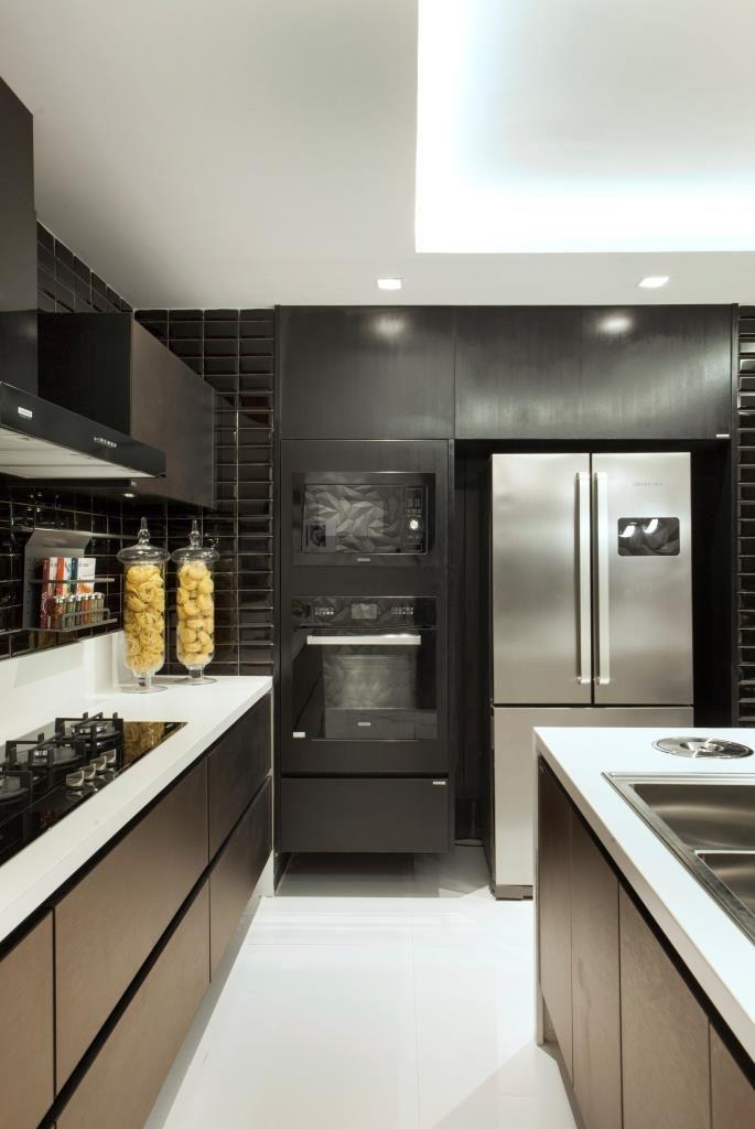 Cozinha preta, branca e bronze com acabamentos modernos e horta