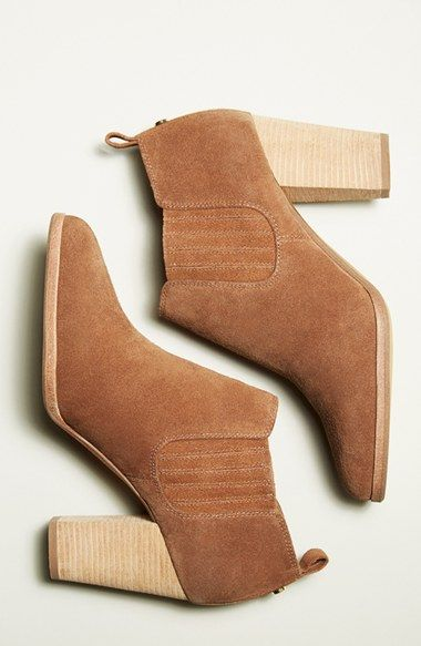 A shapely bootie—fashioned from smooth, burnished black leather or rich caramel suede—dials up the downtown-chic appeal of your daily style, while logo-etched hardware flashes at the heel for a signature flourish.