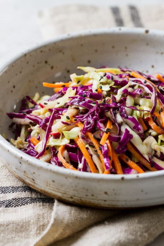 Simple flavorful and delicious this colorful Asian slaw salad features raw veggies and a flavorful dressing made with miso ginger rice wine vinegar and toasted sesame oil. It's colorful and a wonderful mix of flavors!