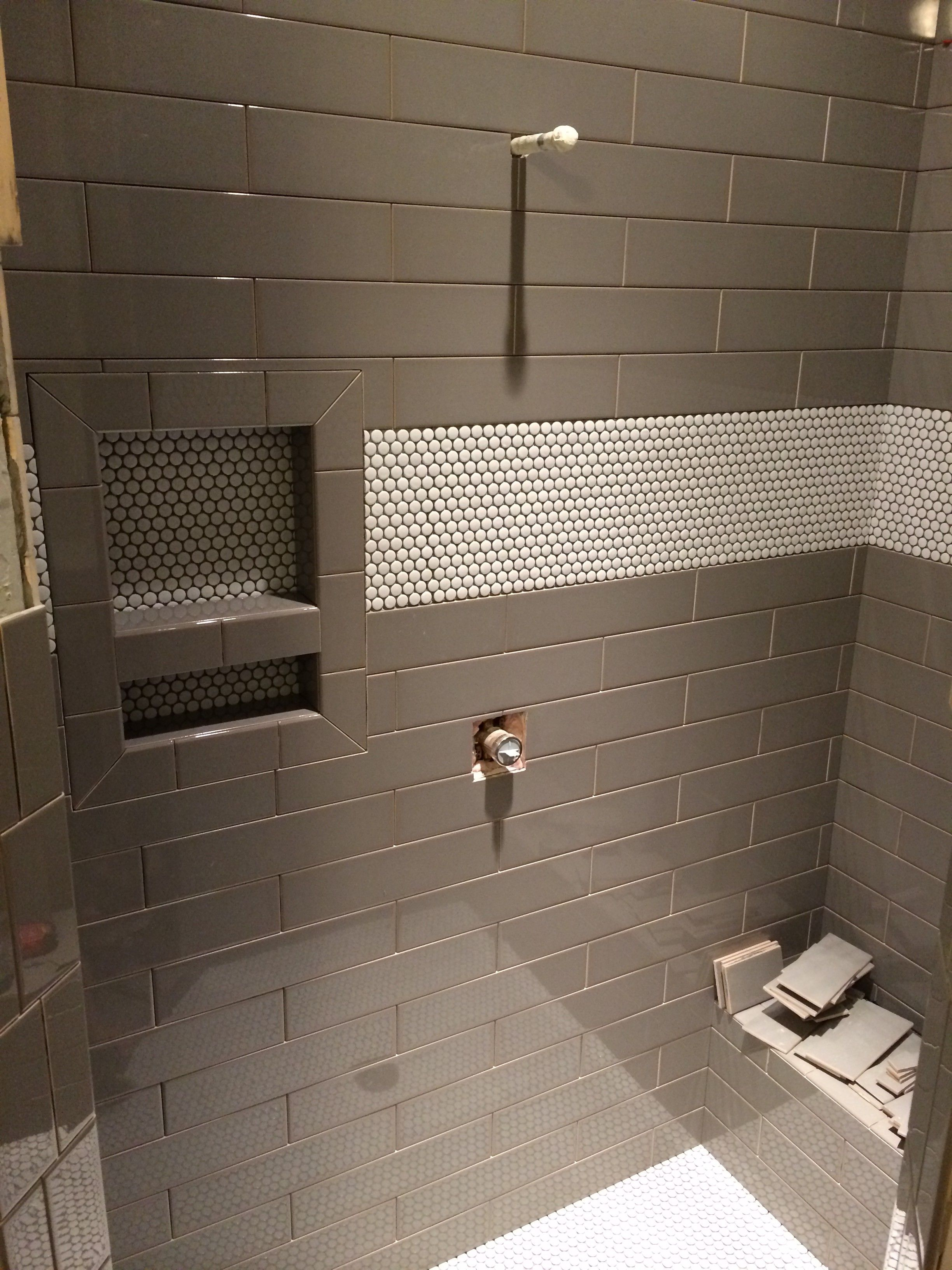 white penny tile and grey brick lay tile in master shower