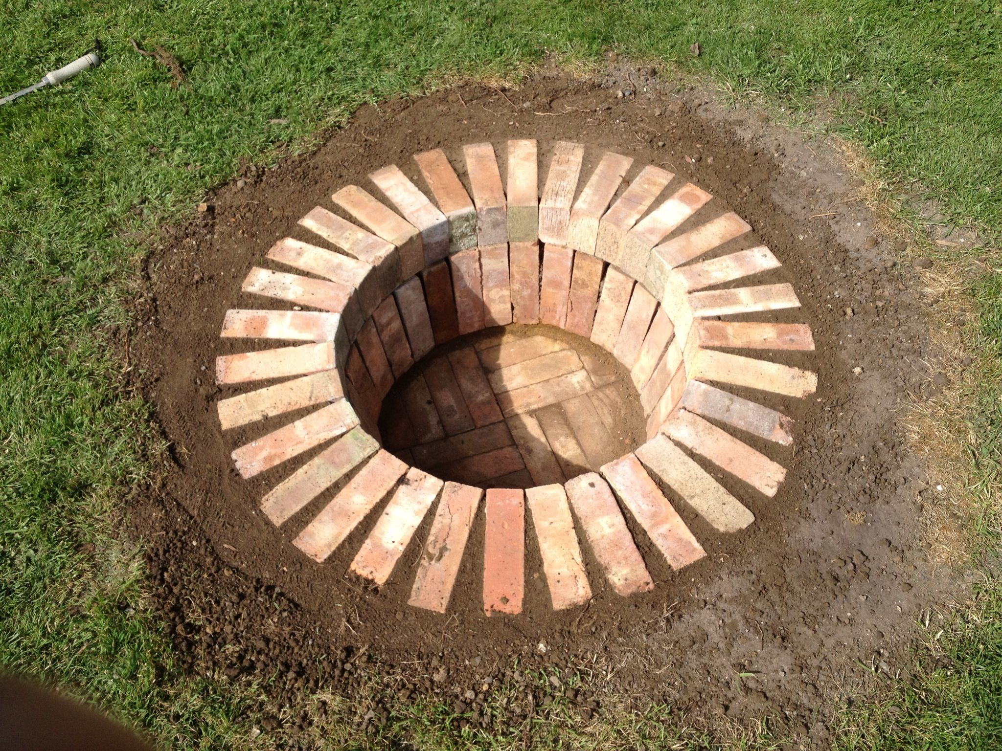 fire pit in the lawn from reclaimed bricks landscaping for