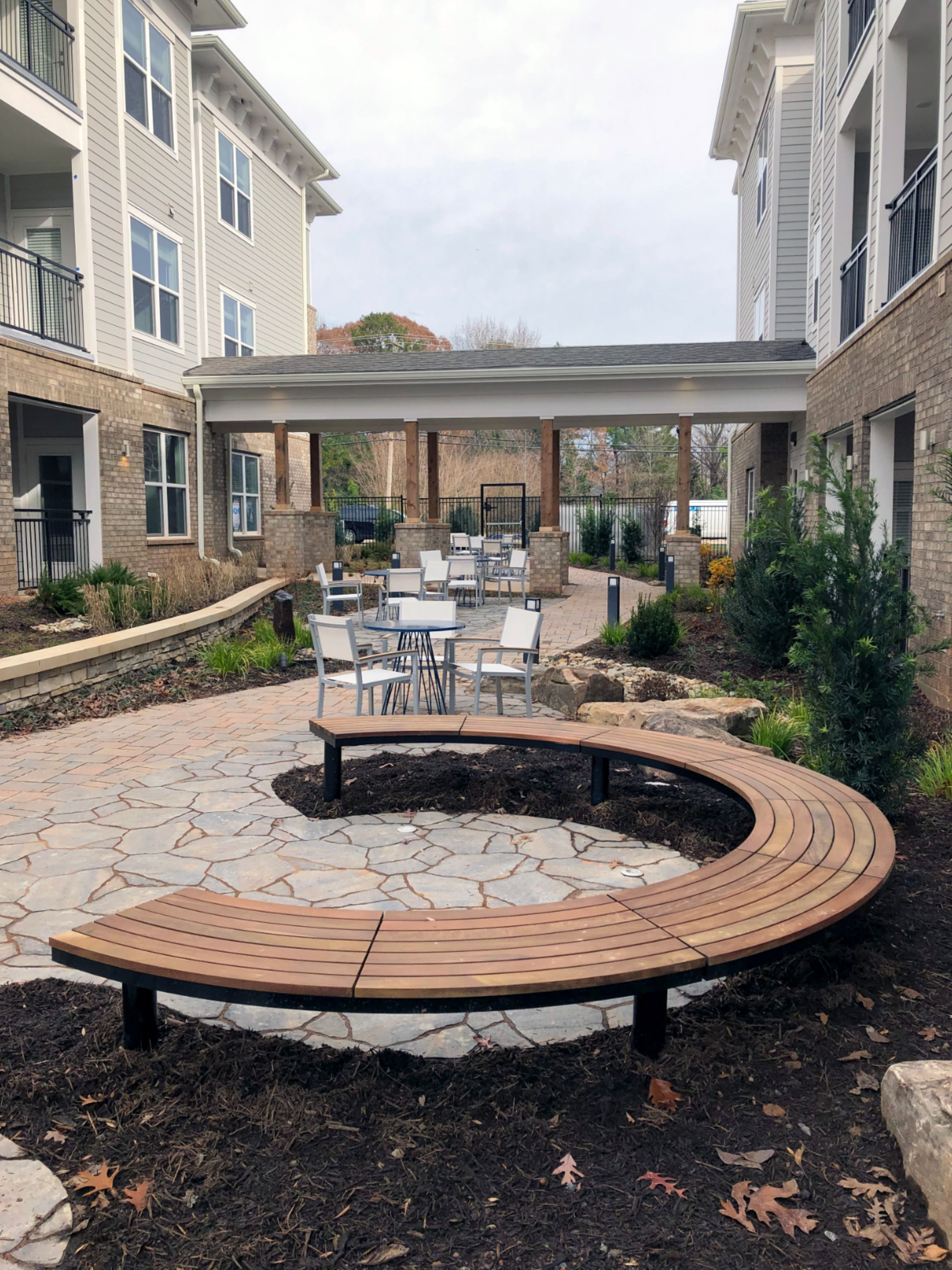 The Ogden Collection curved bench is distinctive and inviting in this residential courtyard. #Maglin #MaglinSiteFurniture #LandscapeArchitecture #LandscapeDesign #CurvedBench #CourtyardDesign