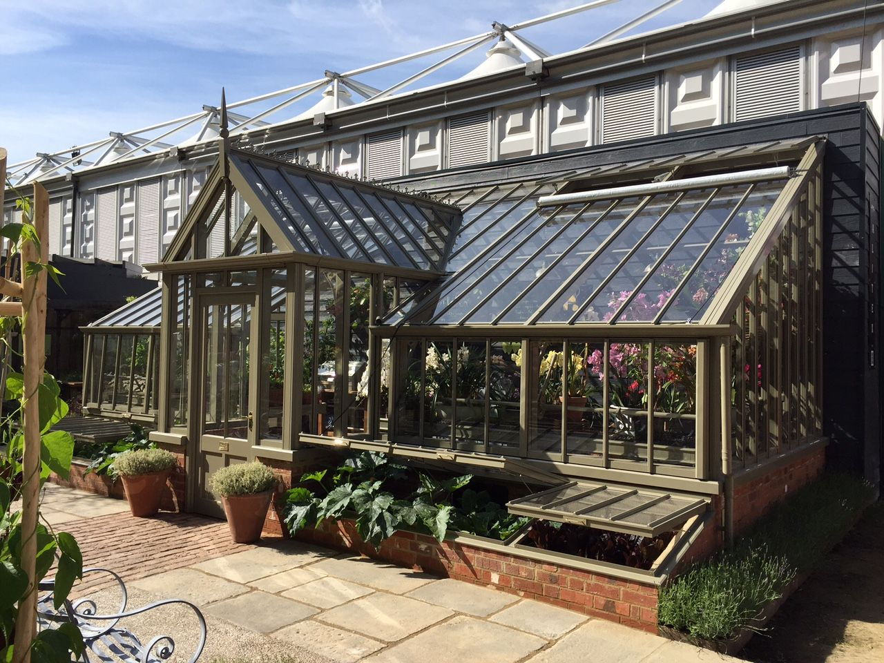 RHS Chelsea 2015. Our largest ever Chelsea structure. A bespoke, mono-pitch, lean-to greenhouse in Green Sand. With Sentry style feature lobby and new cold frames.