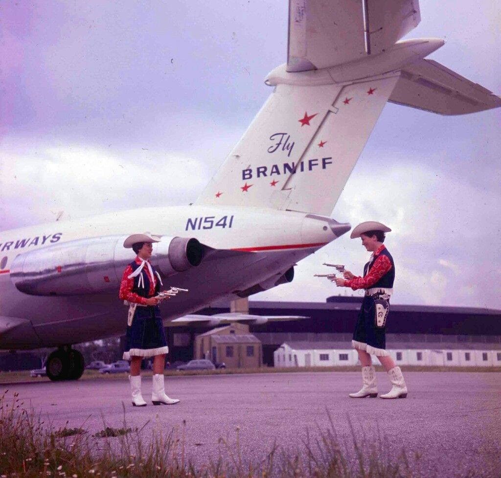 Braniff International BAC-ONE11 at the delivery in England March 1964. Two Braniff hostesses dueling it out Texas style