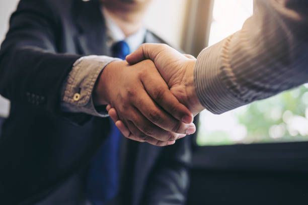 Two business men shaking hands during a meeting to sign ...