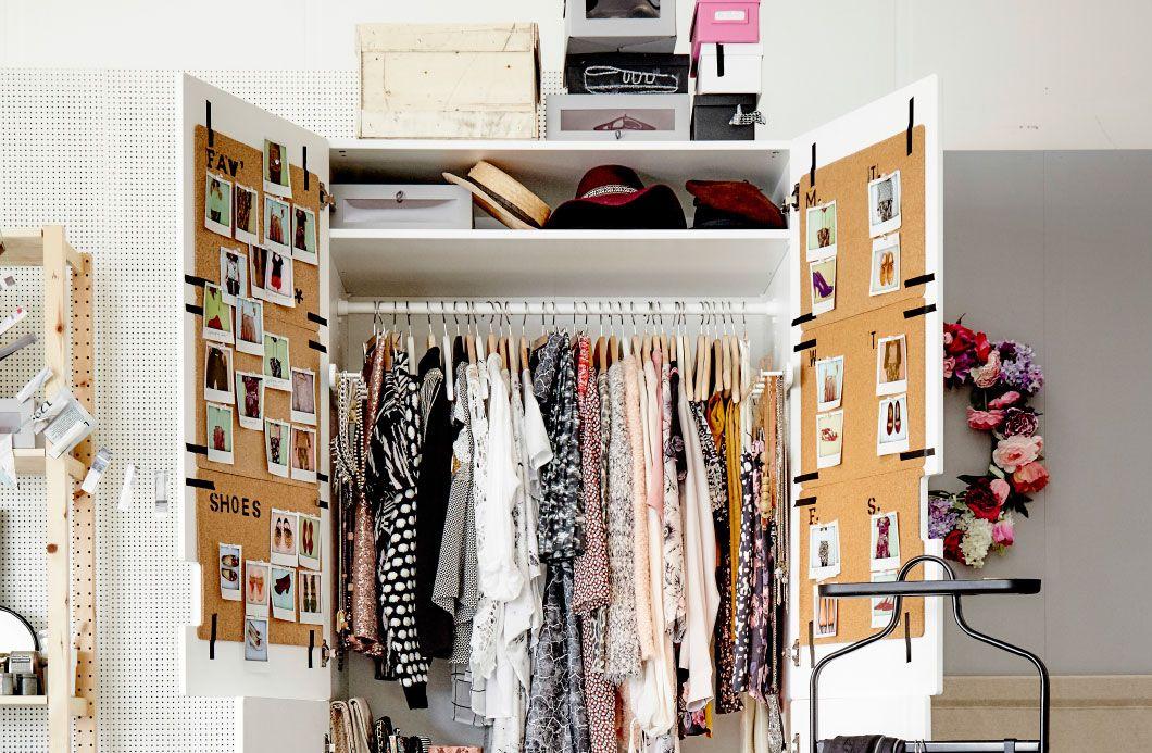 Openstaande witte garderobekast gevuld met kleren