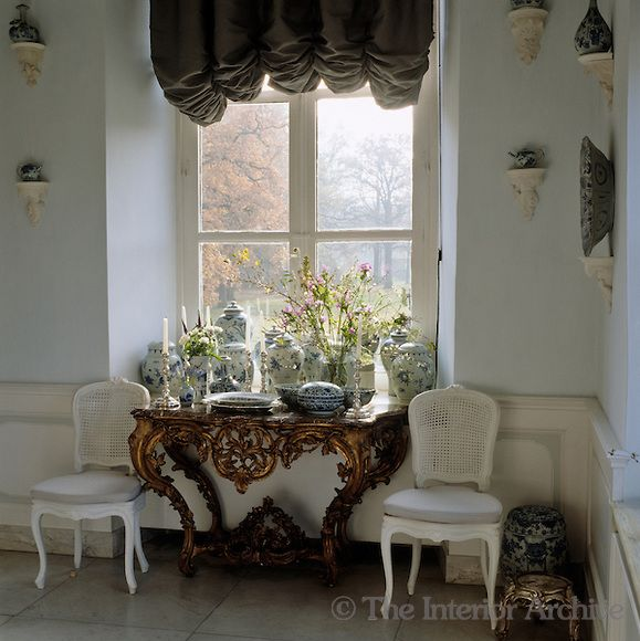 A collection of Chinese blue and white porcelain jars fills the Rococo console table which is flanked by a pair of white cane-backed chairs