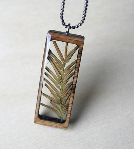When the days are dreary and chilly and altogether too wintry, this lovely little pine necklace is here to remind you of spring. Of blossoms and sunshine and not trudging through the slush on your way to work. Each necklace is made with a dried pine sprig, carefully arranged and encased in clear resin inside a laser-cut oak frame.