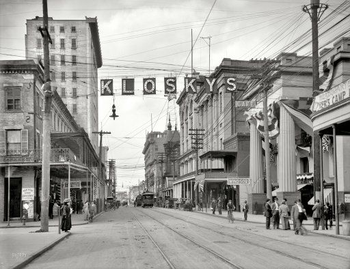 """Mobile, Alabama, circa 1910. """"Royal Street looking north."""" Points of interest include a lineman up a pole and the fickle finger of retail."""