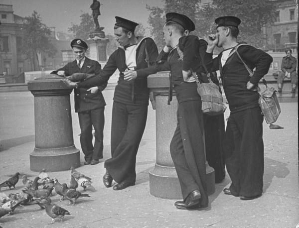 "Officer & several British sailors (clad in their ""tiddly-suits"" aka shore dress) feeding the pigeons in a park while on shore leave. Location:	London, United Kingdom Date taken:	September 1941 Photographer:	David E. Scherman"