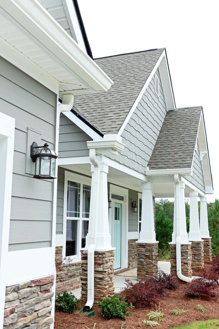 Stone Pillars Add Texture To This Home S Cool Gray Exterior With The Light Aqua Front Door Exterior Paint Colors For House House Paint Exterior House Exterior