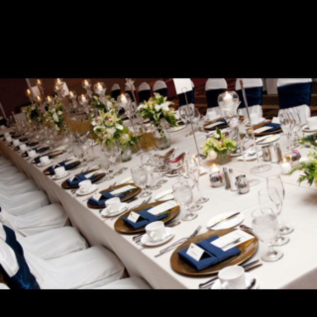 Gold Charges and navy napkins with navy chair ribbons would look even better with navy table cloths - navy napkins