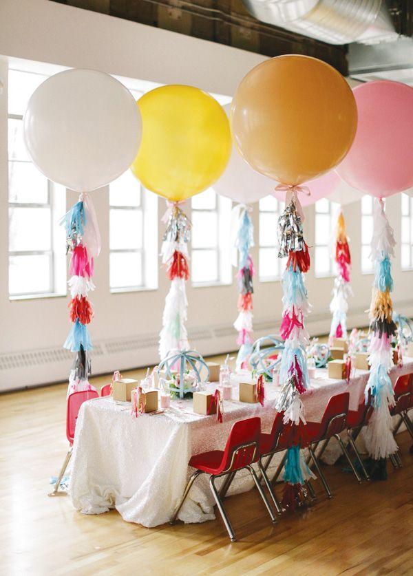 Voor bij de ingang van de Pleats, entree zaal en rondom dansvloer. Witte ballonnen met tassels in de kleuren goud, koraal en mint.