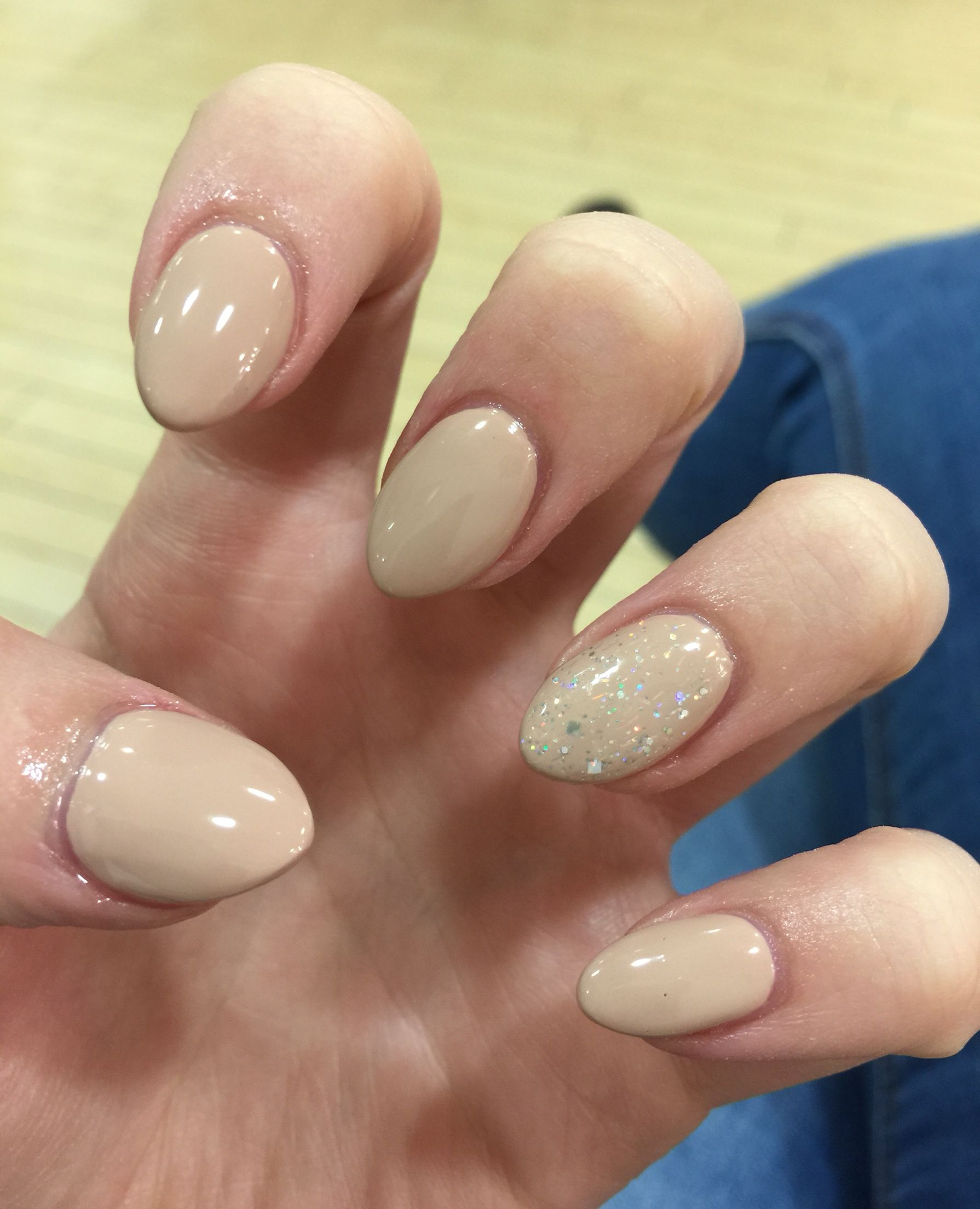 Nude almond shaped nails with sparkly polish on ring finger. These ...
