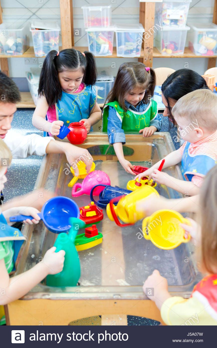 Group Of Nursery Children Playing At A Water Table With Their Teacher Stock Photo Kids Playing Water Table Stock Photos